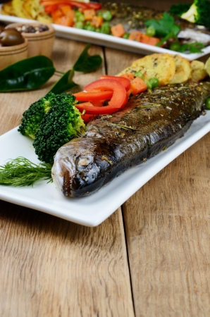 Dish with baked trout and vegetables on the kitchen table Stock Photo - 18708288