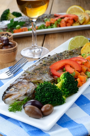 Baked trout vegetables and white wine on the kitchen table Stock Photo - 18708291