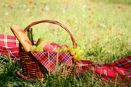 Picnic basket fool of fruits bread and wine with floral meadow at background photo