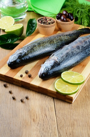 Raw trout on the chopping board with limes photo
