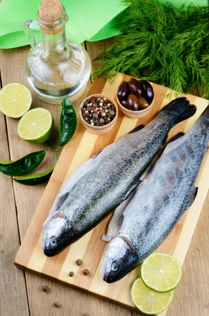 Raw trout on the chopping board with limes Stock Photo - 19080290