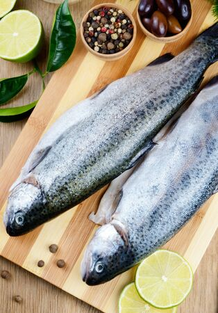 Two raw trout set on the chopping board with lime and spices Stock Photo - 19628840