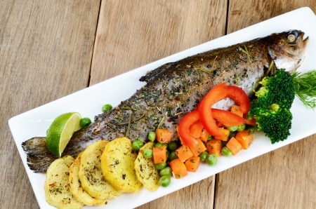trout: Dish with baked trout and vegetables on the kitchen table Stock Photo