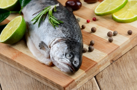 Raw trout on the chopping board with limes Stock Photo - 20228057