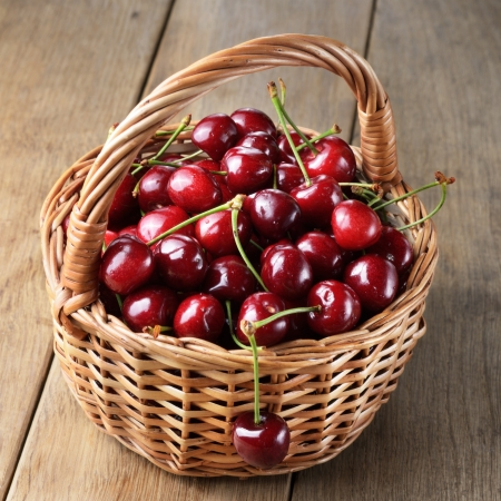Basket of organic Cherries on wooden table Stock Photo - 20228210