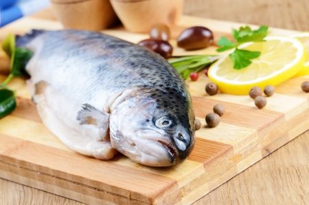 Raw trout on the chopping board with lemon and spices Stock Photo - 20228223