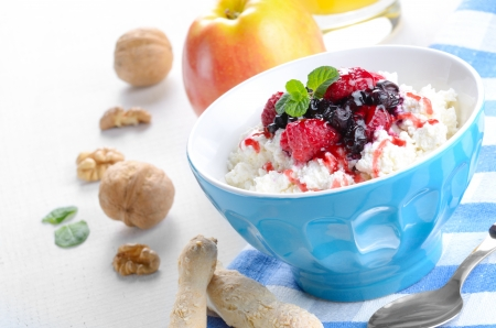 Cottage cheese in blue bowl with raspberries blueberries and mint photo