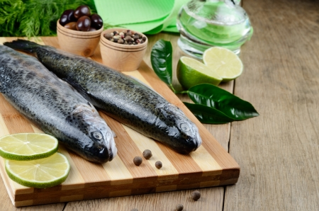 Raw trout on the chopping board with limes Stock Photo - 20380561