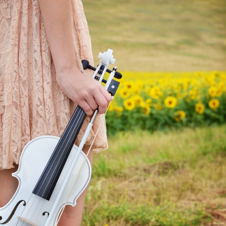 Alone young woman holds violin and bow in her hand photo