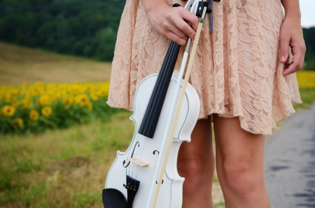 country lifestyle: Alone young woman holds violin and bow Stock Photo