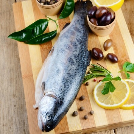 Raw rainbow trout on the chopping board with lemon and spices Stock Photo - 21597404