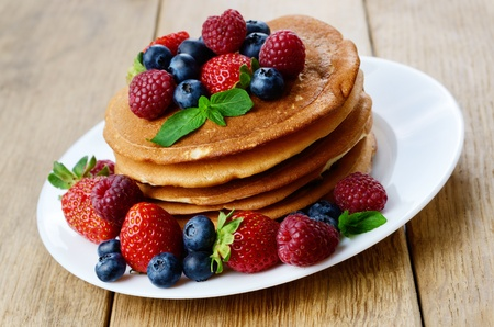 Stack of pancales with strawberries raspberries and blueberries on white plate photo