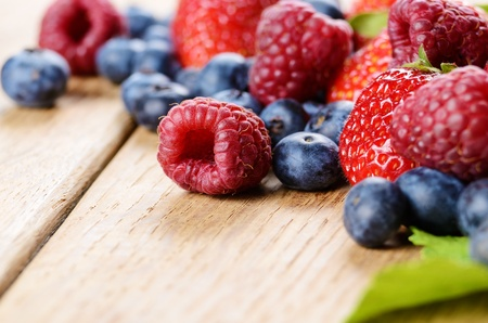 Strawberries raspberries and blueberries on the wooden table macro photo