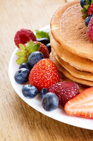 White plate full of pancakes with strawberries raspberries and blueberries photo