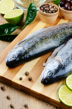 Two raw trout set on the chopping board with lime and spices Stock Photo - 21861603