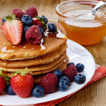 White plate full of pancakes with strawberries raspberries blueberries and honey Stock Photo - 21861637
