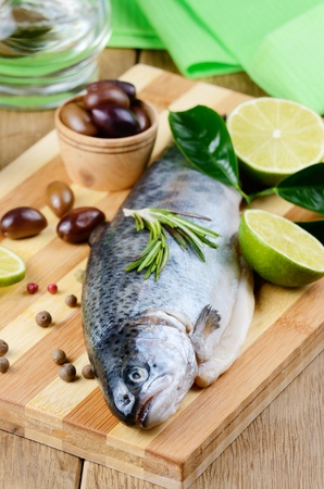 Raw trout on the chopping board with limes Stock Photo - 21861641