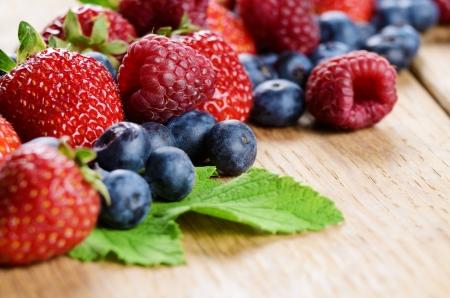 Strawberries raspberries and blueberries on the wooden table macro