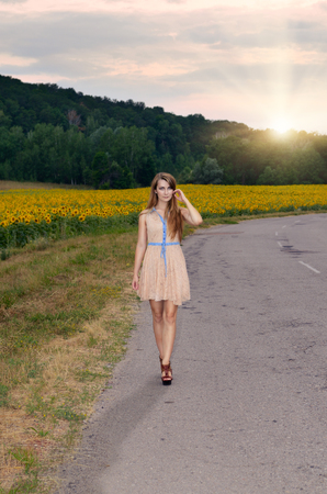 single lane road: Alone young woman in short dress walking by country road Stock Photo