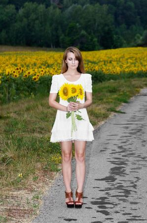 Young woman in white short dress with sunflowers at country road photo