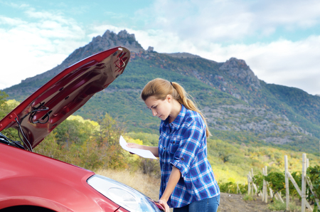 in need of space: Young woman near broken car needs assistance looking under opened hood