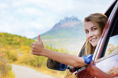 Happy driver woman shows thumb up against mountains background  Travel vacations concept  photo