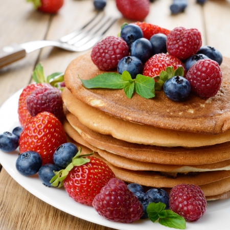 Stack of homemade pancakes with strawberries raspberries and blueberries on white plate