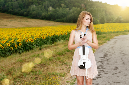 country music: Alone young woman with violin by sunflower field. Country music concept