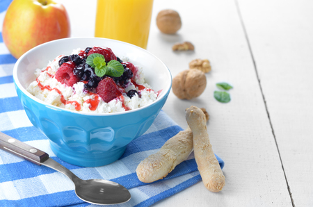 Homemade Cottage cheese in blue bowl with raspberries blueberries and mint photo