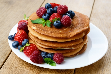 Stack of pancakes with strawberries raspberries and blueberries on white plate photo