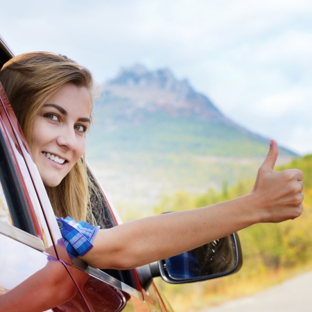 Happy driver woman shows thumb up against mountains background. Travel vacations concept  Reklamní fotografie