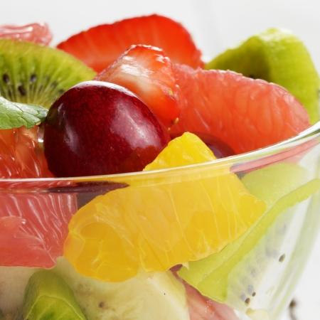 fruit bowl: Glass bowl with mixed fruit salad on the white table