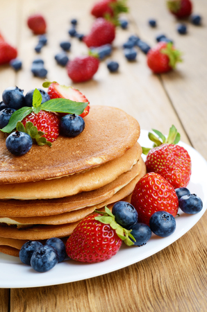 Stack of pancakes with strawberries raspberries and blueberries on white plate Stock Photo - 24476742