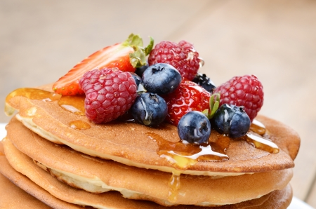 Pancakes with strawberries raspberries blueberries and honey photo