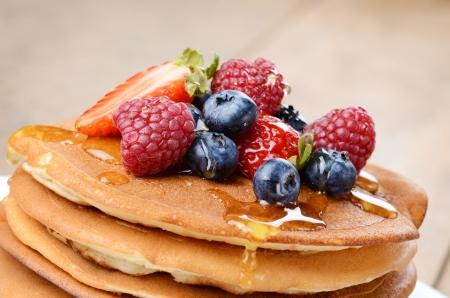 Pancakes with strawberries raspberries blueberries and honey Stock Photo - 24476743