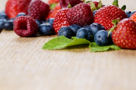 Strawberries raspberries and blueberries on the wooden table macro Stock Photo - 24476846