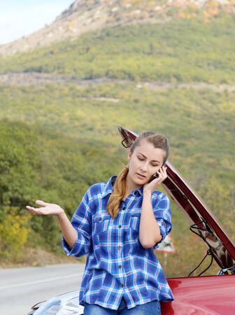 Young woman near broken car speaking by phone needs assistance photo