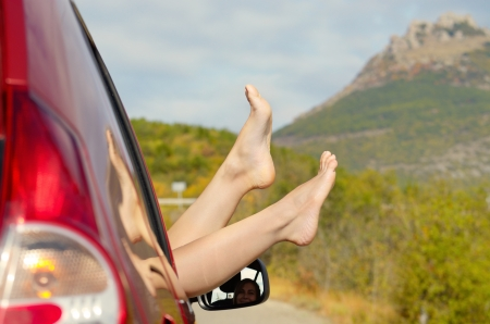 bare foot: Female bare feet stick out of car window on mountain background. Travel concept.