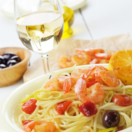 glass plate: Seafood spaghetti pasta dish with shrimps and cherry tomatoes served with white wine