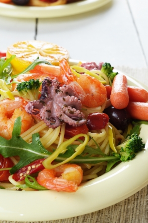 Seafood spaghetti pasta dish with octopus, shrimps, cherry tomatoes and olives photo