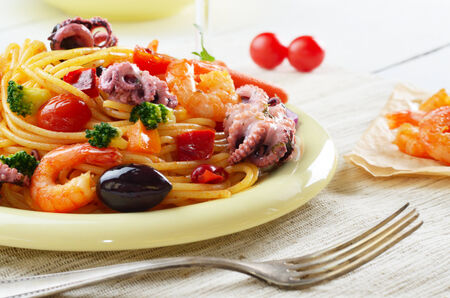 Seafood spaghetti marinara pasta dish with octopus, shrimps, cherry tomatoes and olives photo