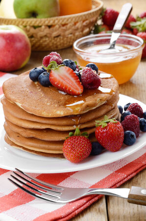 White plate full of pancakes with strawberries raspberries blueberries and honey photo