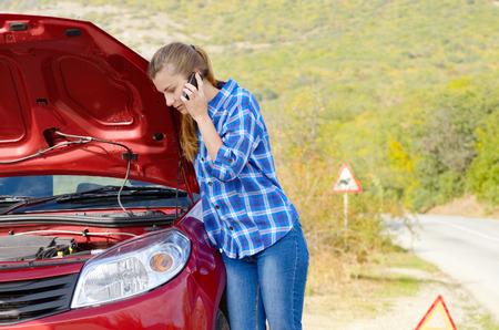 broken car: Mujer joven cerca del coche roto hablando por tel�fono necesite ayuda