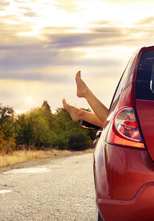 Female bare feet stick out of car window on mountain . Travel concept.