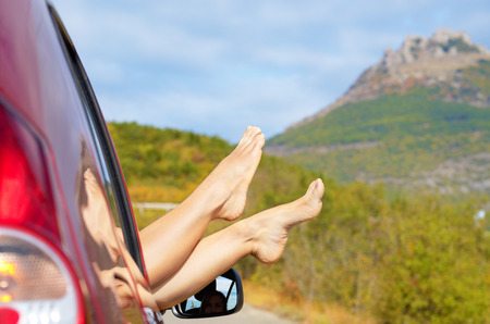 Female bare feet stick out of car window on mountain . Travel concept. photo