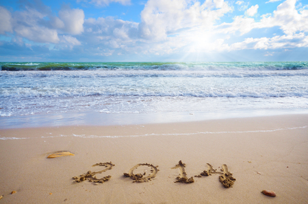 Year 2014 coming concept on beach sand, the water is washing out digits photo
