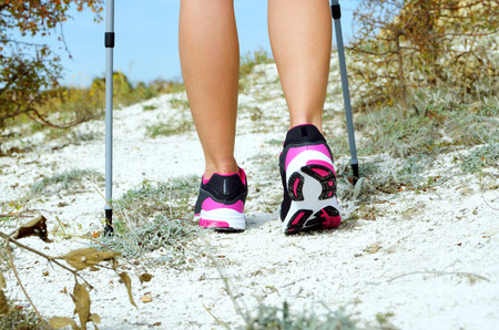 Female feet and trekking stick on the path photo