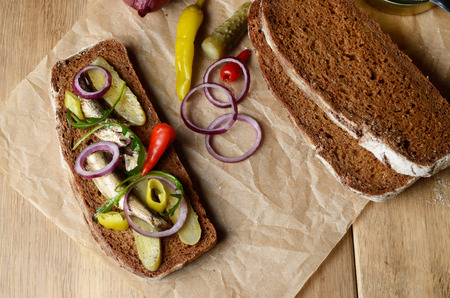 sprat: Sprat sandwich with pickled cucumber onion and peppers on the kitchen table