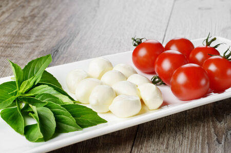 Caprese salad in shape of Italian flag on the white plate photo