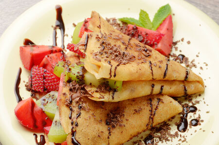 chocolate mint: Homemade tasty crepes with strawberries, kiwi and chocolate syrup Stock Photo
